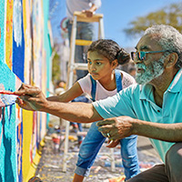 man and girl painting a wall